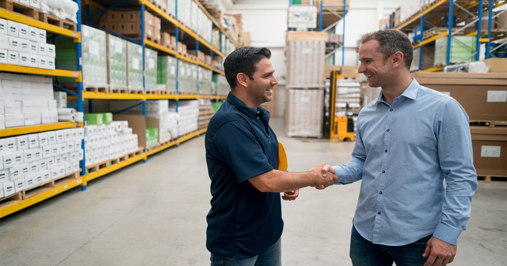 Supply Chain Professionals Shaking Hands in Warehouse